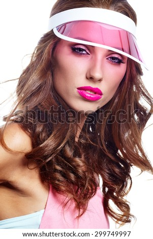 woman looking through the pink sun visor at camera