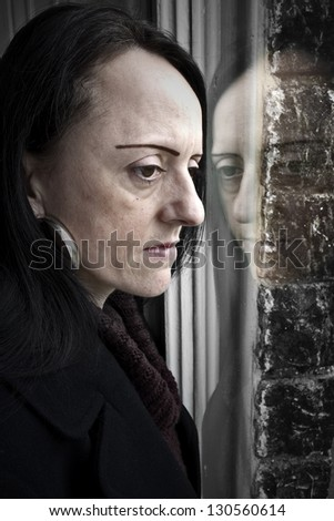 woman looking through window worried or depressed portrait - stock photo
