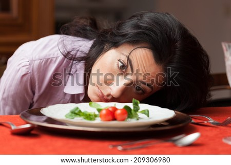 Woman looking to a little salad is tired about diet. - stock photo