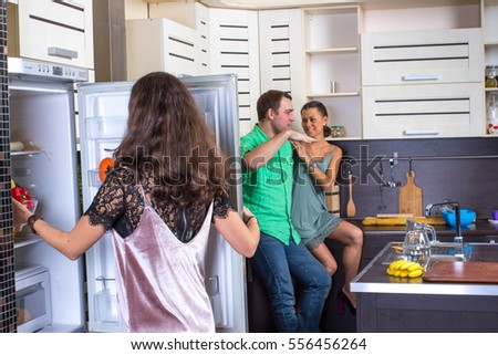 Woman looking to fridge with couple on background.
