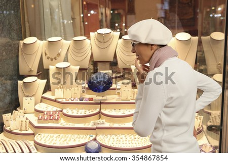 Woman looking to showcase or shop window. Shopping woman chooses jewelry in store - stock photo