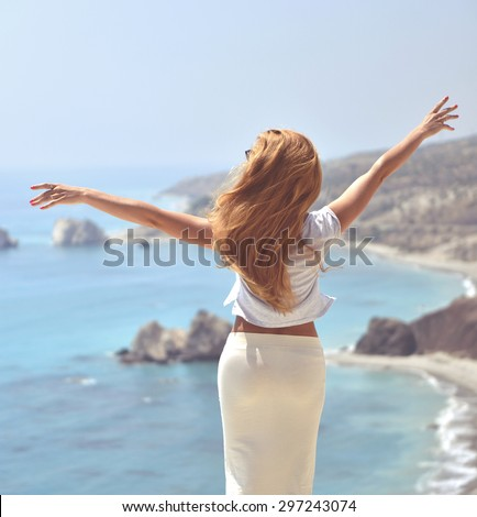 Woman looking to the sea near Aphrodite birthplace with windy hair on Cyprus back view - stock photo
