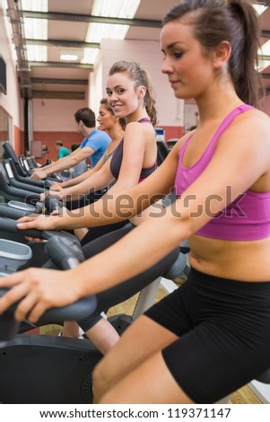 Woman looking to the side on exercise bicycle in the gym