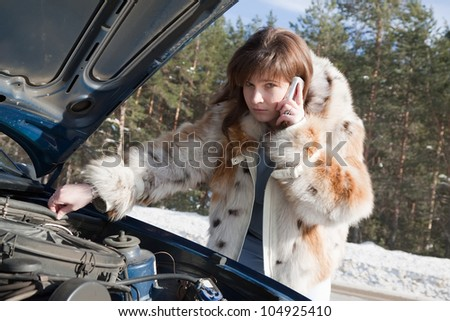woman looking under the car hood in winter day - stock photo