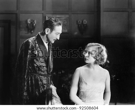 Woman looking unhappy at a man in a robe - stock photo