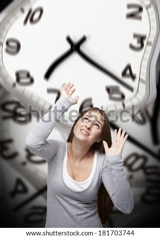 Woman looking up and trying to stop a big warped clock above her with a background made of warped clocks - stock photo