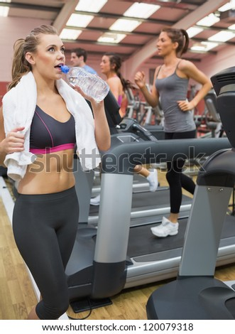 Woman looking up drinking water in the gym - stock photo