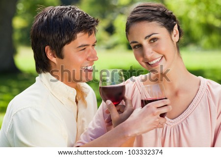 Woman looks ahead while smiling as she is linking arms with her friend and holding glasses of red wine in a park - stock photo