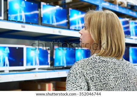 Woman looks at LCD TVs in supermarket - stock photo