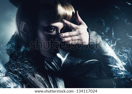 woman looks at silver light through fingers - stock photo