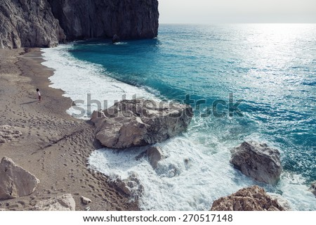 Woman looks at the sea in the island Lefkada, Greece. - stock photo