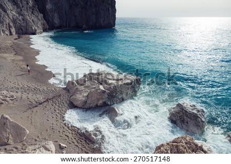 Woman looks at the sea in the island Lefkada, Greece. - stock photo
