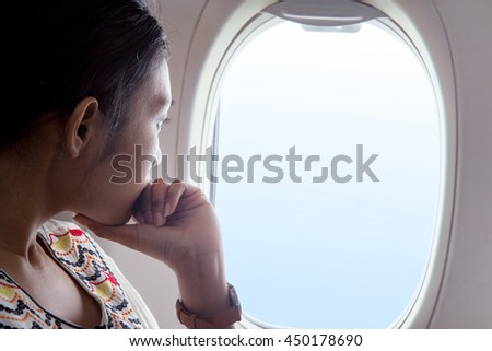 Woman looks out the window of an flying airplane. Young passengers are traveling by plane, watching the sky from above.