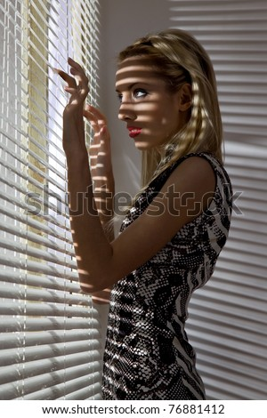 Woman looks out the window through the blinds - stock photo