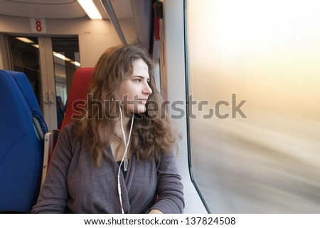woman looks out the window while sitting in the train. - stock photo
