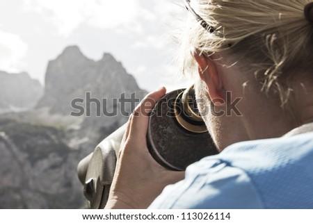 Woman looks through telescope - stock photo