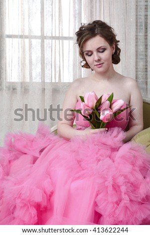 woman looks towards the violation of thinking on a pink background. Beautiful woman portrait in dress smiling fresh happy. Pretty mixed race Caucasian brunette fashion model. - stock photo