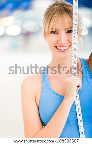 Woman loosing inches at the gym holding a tape measure