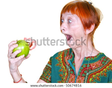 Woman losing her false teeth by biting into an apple - stock photo