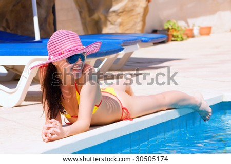 Woman lying and relaxing by a large swimming pool on holiday - stock photo