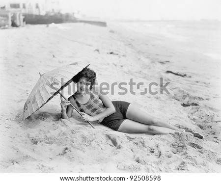 Woman lying at the beach with a sun umbrella - stock photo