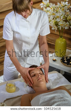 Woman lying down at luxury spa room getting head massage - stock photo