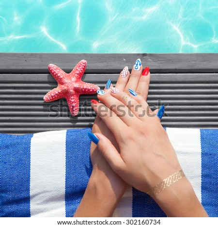 Woman lying down by the pool, marine sailor gel nails close up summer beauty concept - stock photo