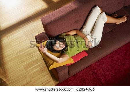 Woman lying down on sofa in her new house. Horizontal shape, high angle view, full length, copy space - stock photo