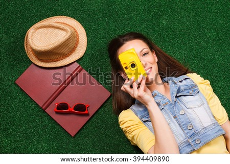 Woman lying down on the  grass and photographing.Woman photographing - stock photo
