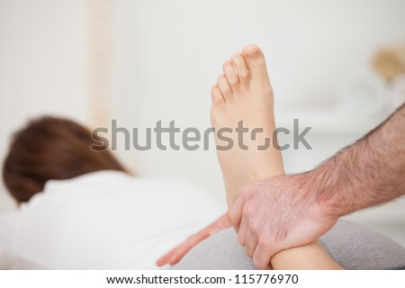 Woman lying forward while a physio manipulates her foot in a room - stock photo