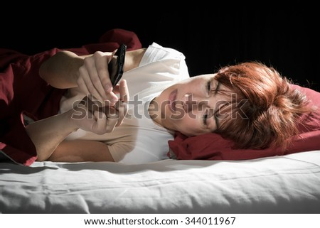 Woman lying in a bed looking at the phone screen.