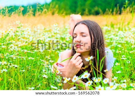 woman lying in a field and smelling a daisy - stock photo