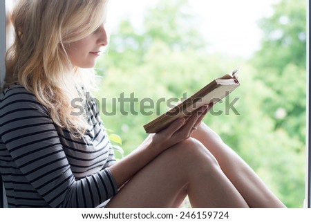 Woman lying in a garden and enjoying book reading - stock photo