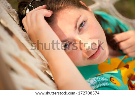 woman lying in a hammock and looking at the camera - stock photo