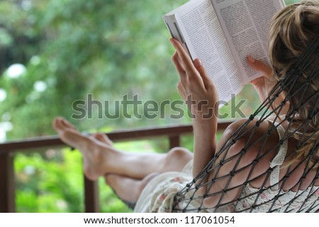Woman lying in a hammock in a garden and enjoying a book reading - stock photo