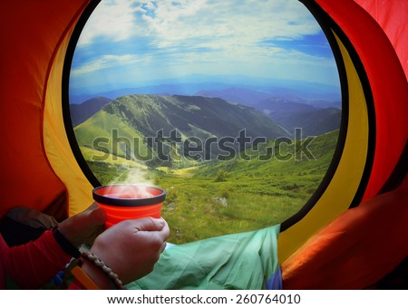 Woman lying in a tent with coffee ,view of mountains and sky in Carpathians mountains, Ukraine,  - stock photo