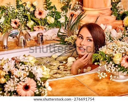 Woman lying in bath  applying moisturizer at bathroom. - stock photo