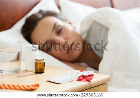 Woman lying in bed having autumn flu - stock photo