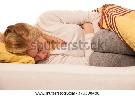 Woman lying in bed holding belly because of the pain in stomach. - stock photo