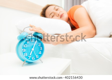 Woman lying in bed turning off an alarm clock in the morning at 7am - stock photo
