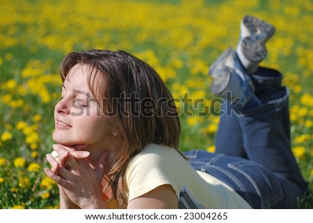 Woman lying in field of dandelions with face turned to sun