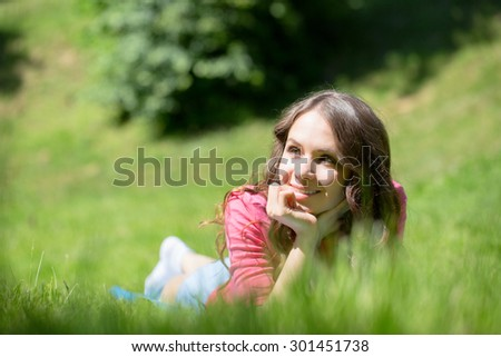 Woman lying in grass and smiling - stock photo