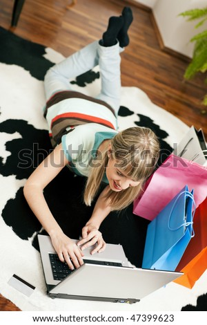 Woman lying in her home living room on floor shopping or doing banking transactions online in the Internet, emphasized by shopping bags in the background and a credit card on the floor - stock photo