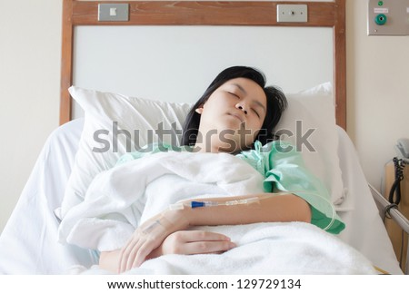 Woman lying on a bed while closing her eyes in hospital - stock photo