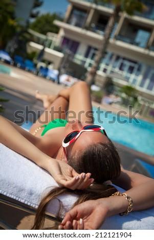 woman lying on a deckchair, enjoying summer near the pool. (focus on face) - stock photo