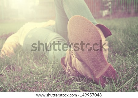 Woman lying on a grass relaxing with jeans and traveling shoes, close-up on her soles,  - stock photo