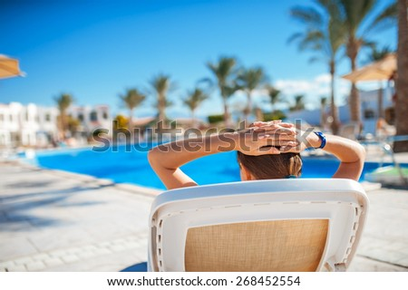 Woman lying on a lounger near a swimming pool in Egypt. - stock photo