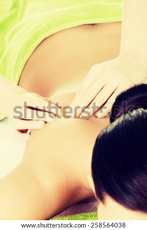 Woman lying on a massage table and is being massaged. - stock photo