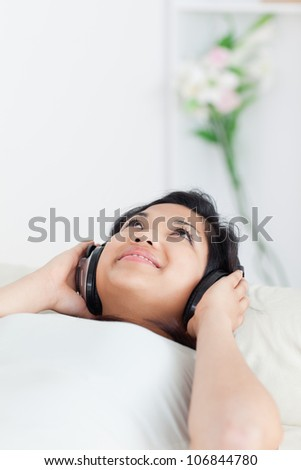 Woman lying on a sofa with headphones on in a living room