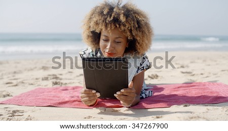 Woman lying on beach towel and using a tablet computer on a beach - stock photo